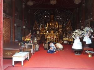 Buddhit Monk blessing kneeling worshipers