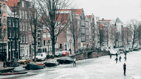 Canals in Amsterdam are frozen and making your way around town has never been so fun