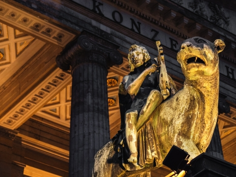 """alt=""""Bronze lion and angel statue in front of the Berlin Concert Hall"""""""